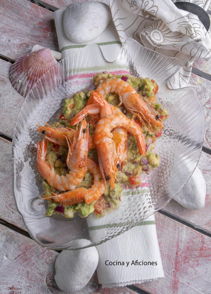 un plato de cristal con forma de pen con el guacamole y encima los langostinos