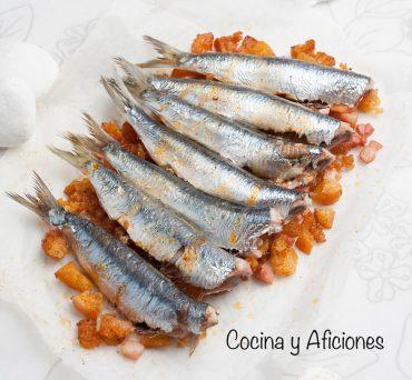 Sardinillas al horno con aceite de pimenton sobre ricas migas crujientes, receta sencilla